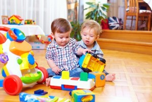 two cute baby toddlers playing in nursery room